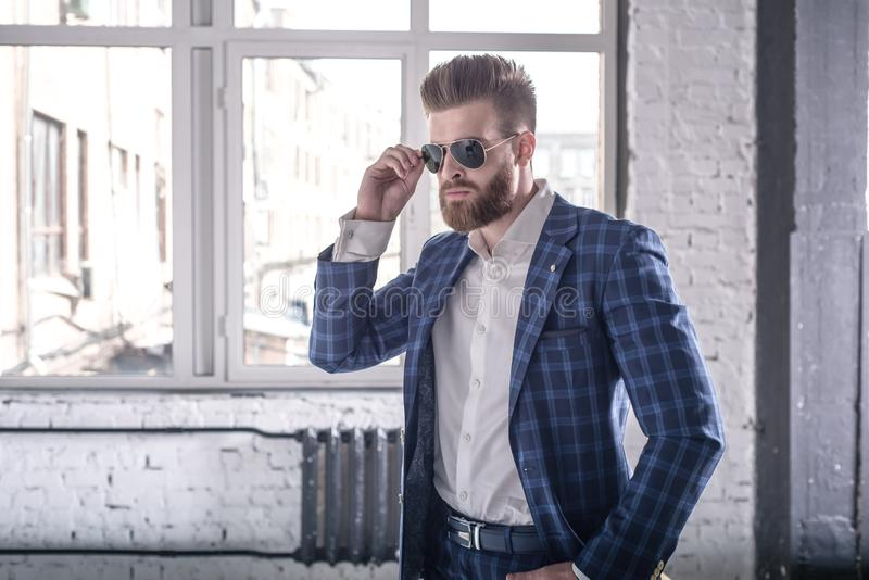 Time to go. Portrait of handsome young man in full suit and suspenders looking away and keeping sunglasses by his hand while royalty free stock image