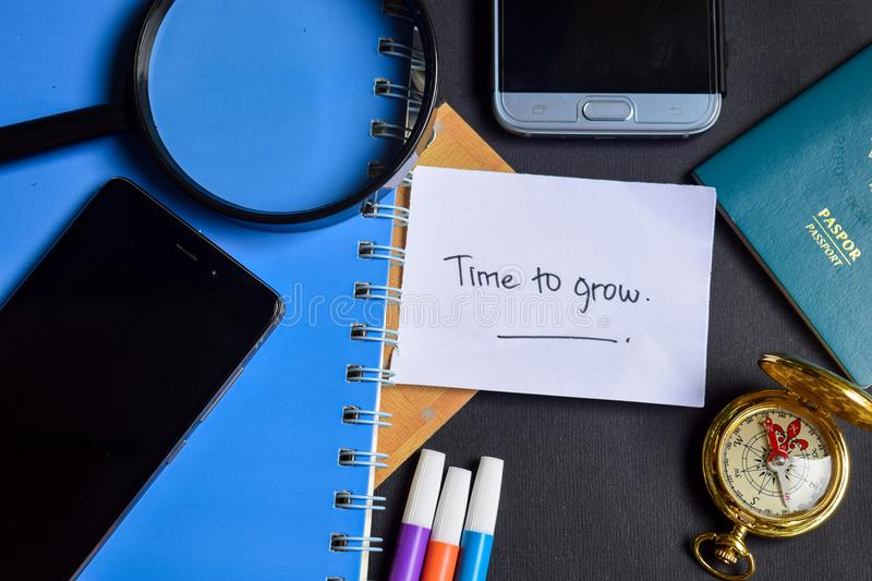 Time to Grow now written on paper. passport, magnifying glass, Compass, Smartphone royalty free stock photos