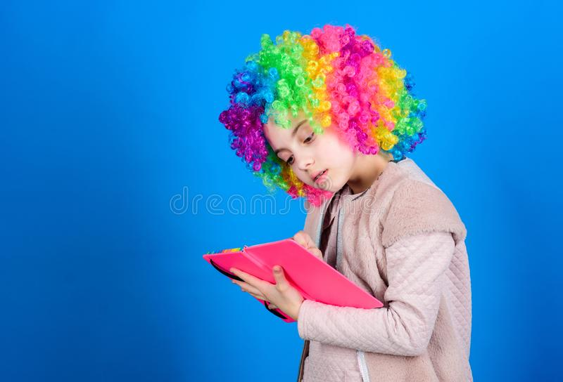 Time to have fun. Circus school. Study hard. Ridiculous story. Reading funny book. Literature club. Jokes book concept. Kid colorful curly wig artificial hair royalty free stock photos