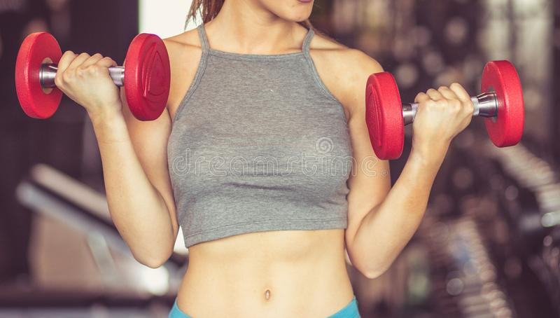 Time to hit the gym. Sportswoman working exercise for hands with weight. Close up royalty free stock image