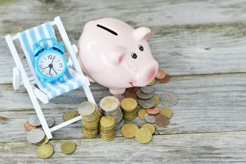 Time to invest your savings concept with pile of money , alarm clock and piggy bank stock image