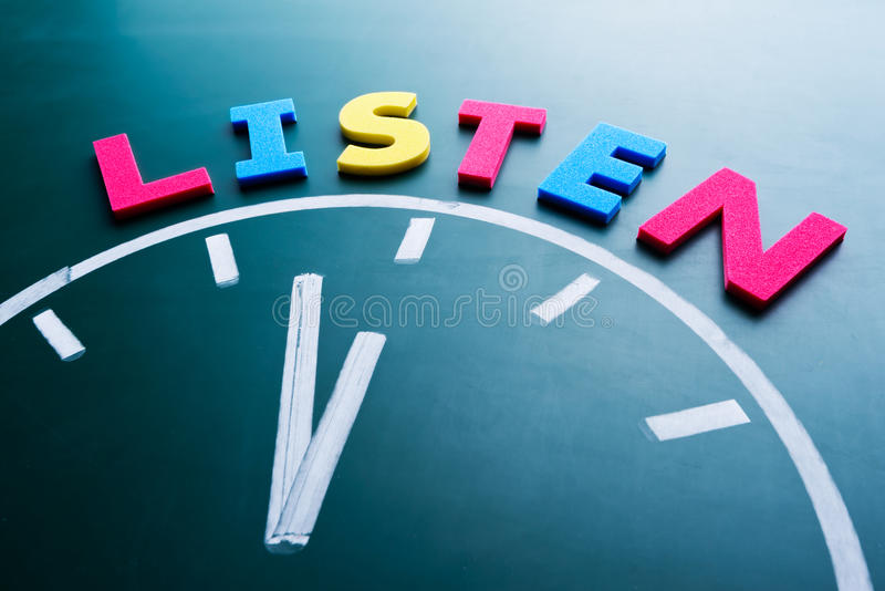 Time to listen concept. Color word and clock on blackboard stock image
