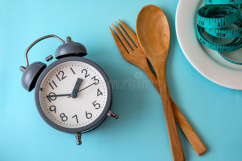 Time to lose weight , eating control or time to diet concept , a alarm clock with healthy tool concept decoration on blue. Time to lose weight , eating control stock images