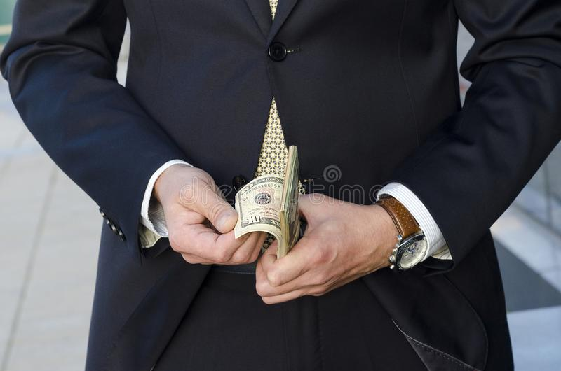 Time to make money. businessman in a suit with a wad of cash. businessman recounts profits. stock photos