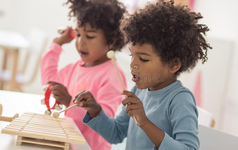 Time to make some music. Children in preschool stock photo