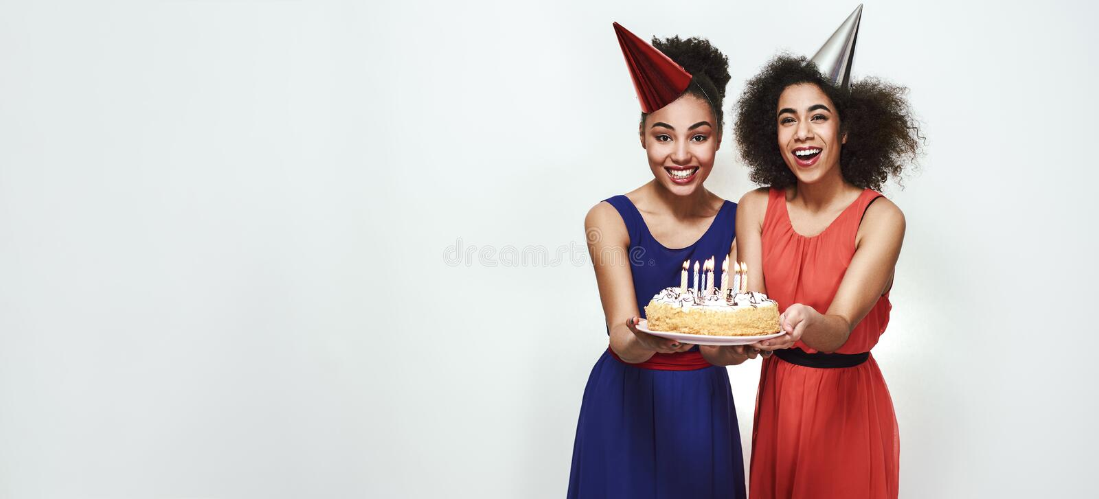 Time to make a wish! Wide photo of happy young afro american women in party hats holding a cake with candles while royalty free stock photo