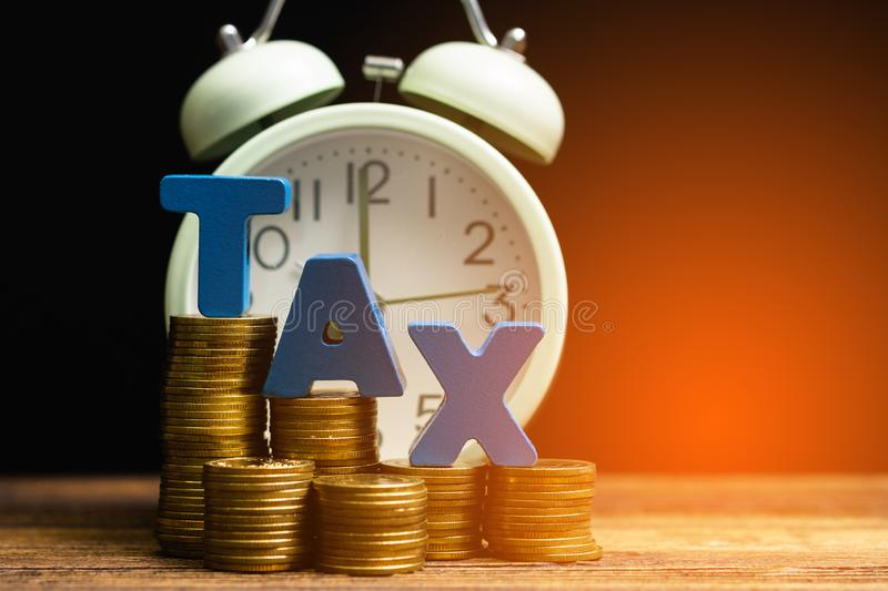 Time to pay TAX concept. TAX alphabet with stack of coin and vintage alarm clock on wooden working table in dark background, royalty free stock photography