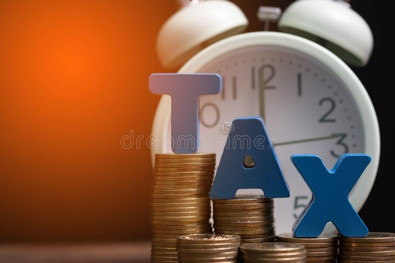 Time to pay TAX concept. TAX alphabet with stack of coin and vintage alarm clock on wooden working table in dark background, royalty free stock images