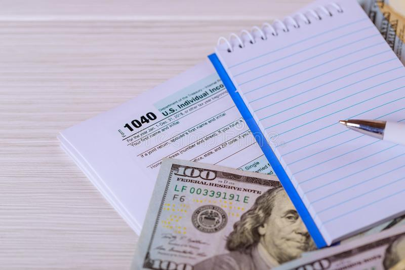 The pen, notebook and dollar bills is lies on the tax form 1040 U.S. Individual Income Tax Return. royalty free stock photography