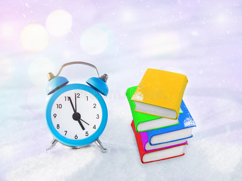 Time to read. Book and vintage alarm clock on the snow. The concept of Christmas and New Year. Magic composition. Switched to winter time. Good morning royalty free stock photography