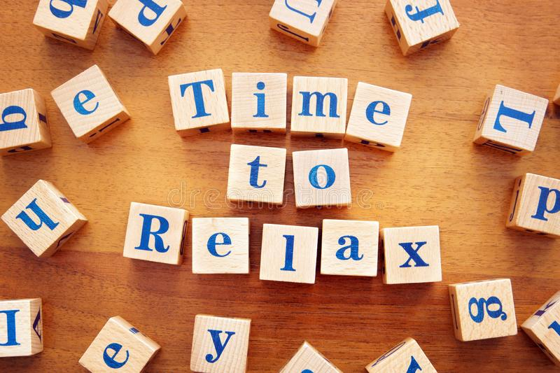 Time to relax. Conceptual image with the text made from wooden cubes. On a desk royalty free stock image