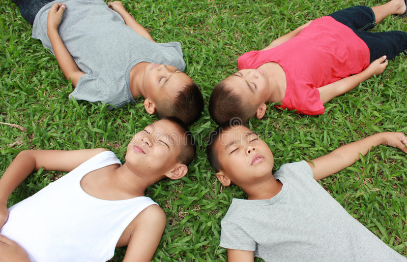 Time to relax!. Four boys sleeping in the park royalty free stock photos