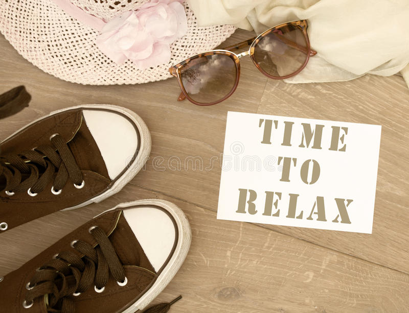 Time to relax. Text with old worn sneakers and travel accessories in the background royalty free stock photography
