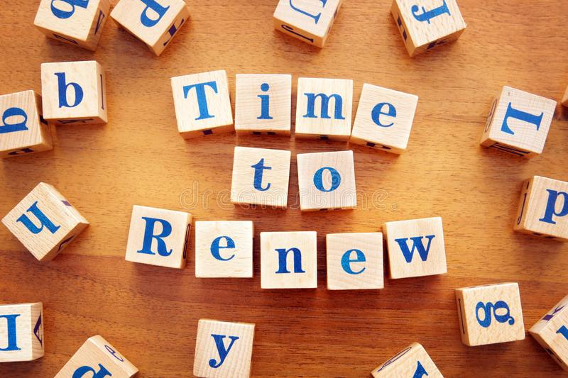 Time to renew. Conceptual image with the text made from wooden cubes. On a desk royalty free stock image