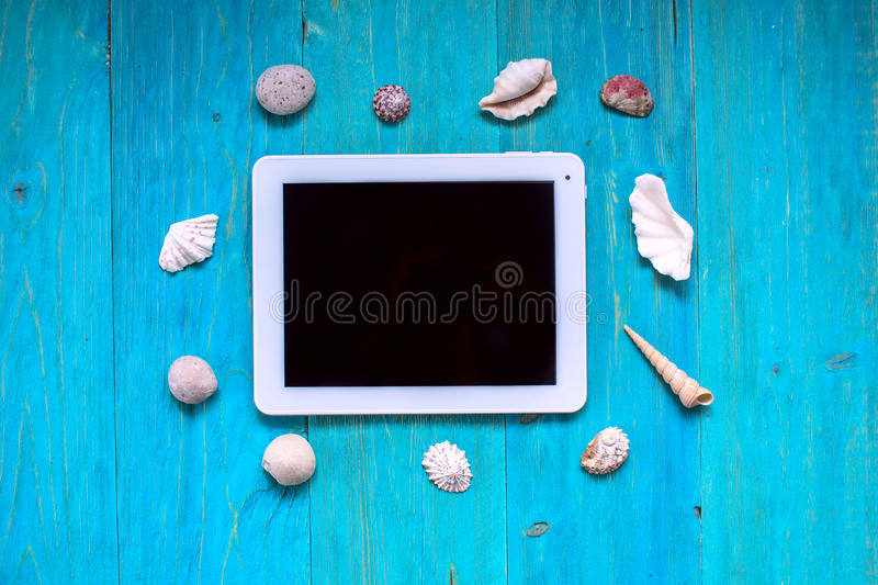 Time to rest, tablet, seashells, blue wood background, royalty free stock photos