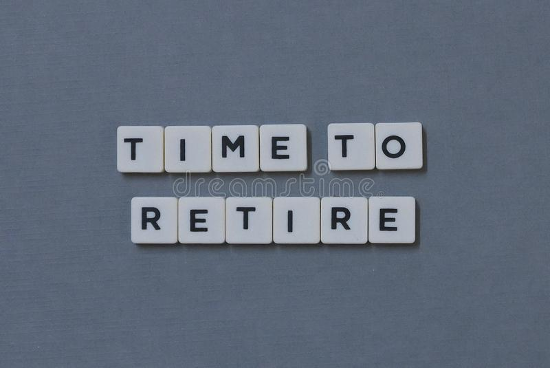 ' Time To Retire ' word made of square letter word on grey background. Retirement, old, clock, business, glass, timer, hour, deadline, pension royalty free stock images