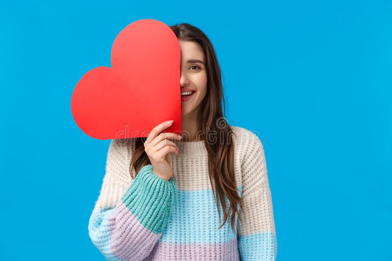 Time to say i love you. Cheerful dreamy and cute caucasian brunette woman cover half face with big red heart sign. Smiling, express affection and symapthy on royalty free stock photography