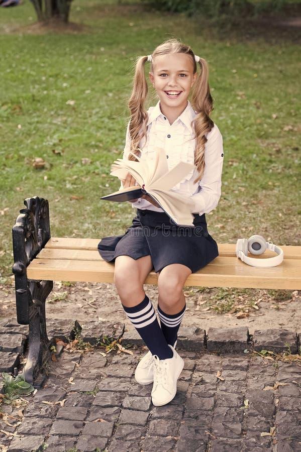 Time to study. Schoolgirl reading book. Little genius. Schoolgirl relaxing sit bench with book. Studying in school yard. Smart schoolgirl. Student adorable royalty free stock image