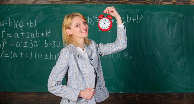 Time to study. Welcome teacher school year. Experienced educator start lesson. She cares about discipline. What time is. It. Woman teacher hold alarm clock stock photo