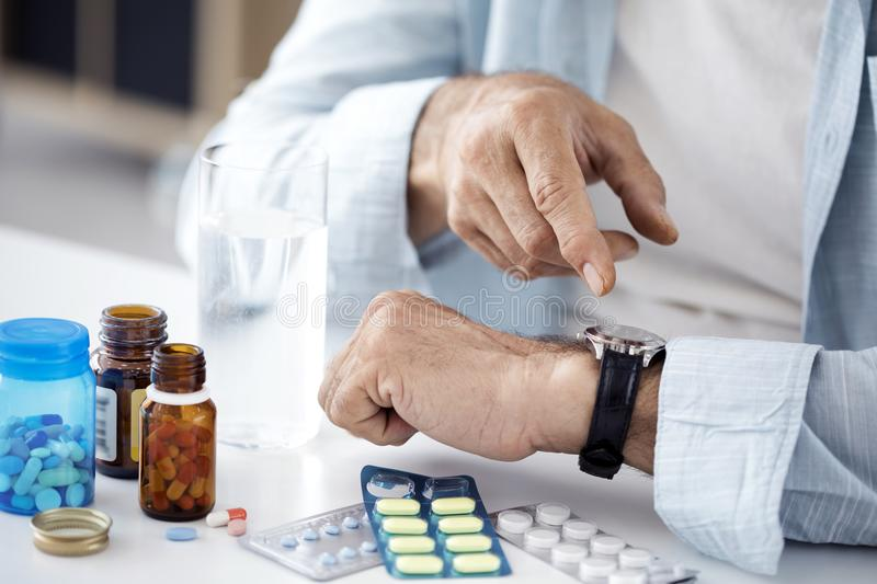 Time to take pills for old man stock photos