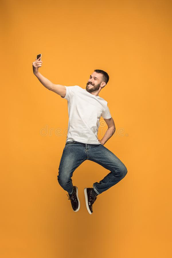 Time to take selfie. Full length of handsome young man taking selfie while jumping. Against orange studio background. Mobile, motion, movement, business stock photo