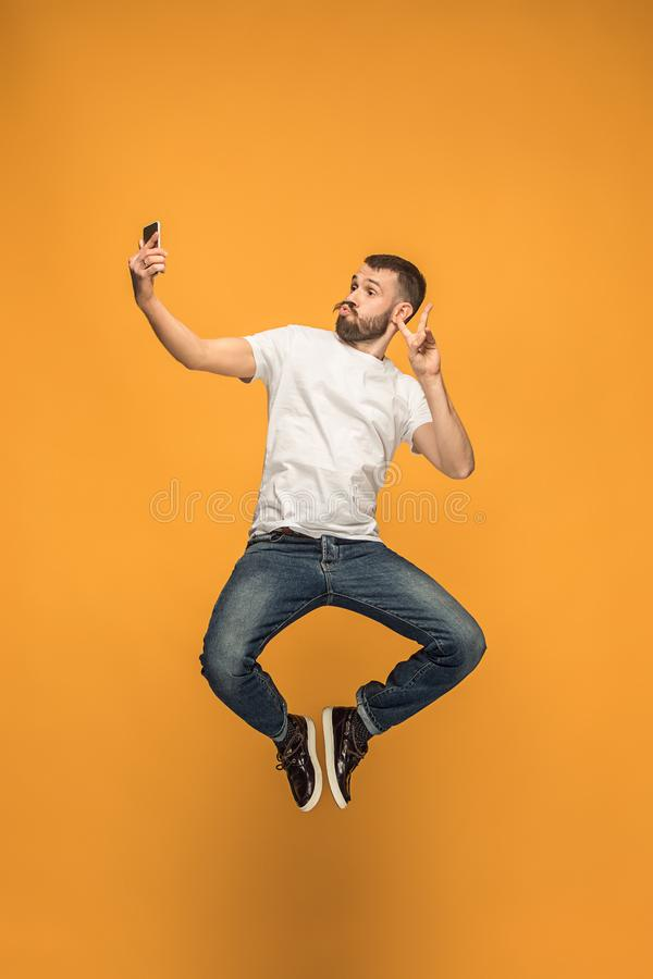 Time to take selfie. Full length of handsome young man taking selfie while jumping royalty free stock images