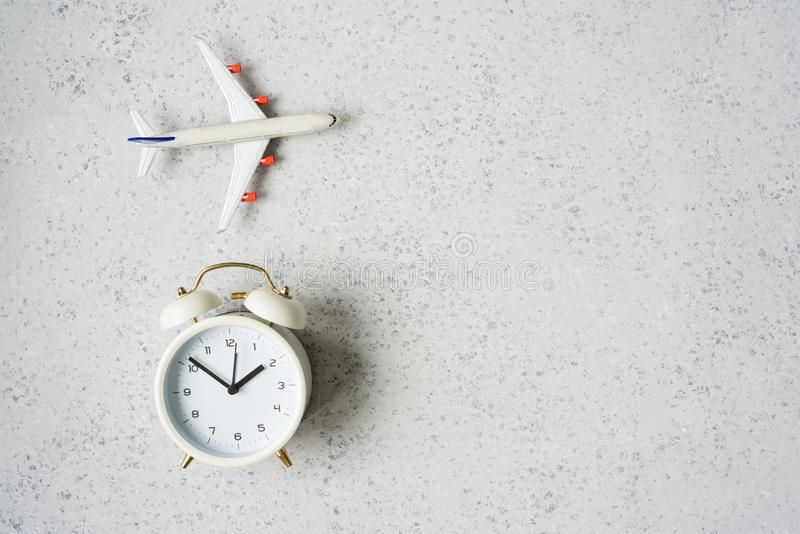Time to travel concept. plastic plane jet toy passenger with alarm clock.  stock image