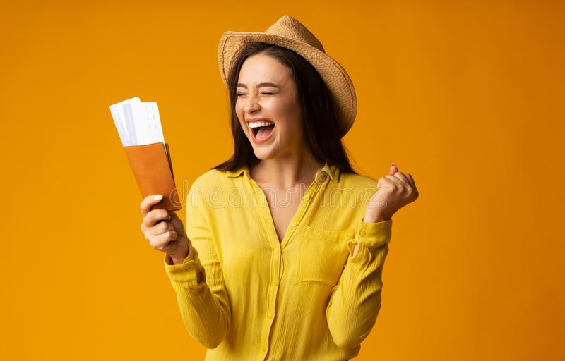 Gladful Woman Traveler Holding Tickets And Passport Over Yellow Background stock photos