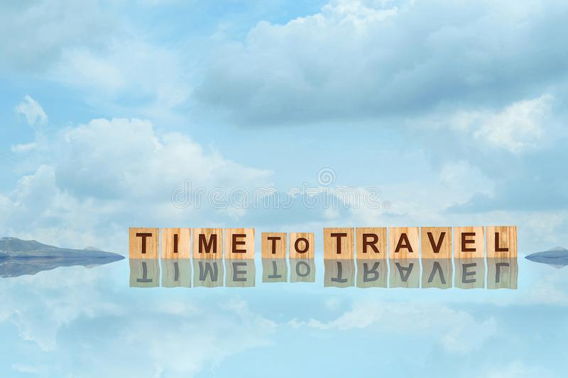 Time To Travel word written on wooden blocks with reflection, against the blue sky with beautiful clouds. Copy space. Travel royalty free stock images