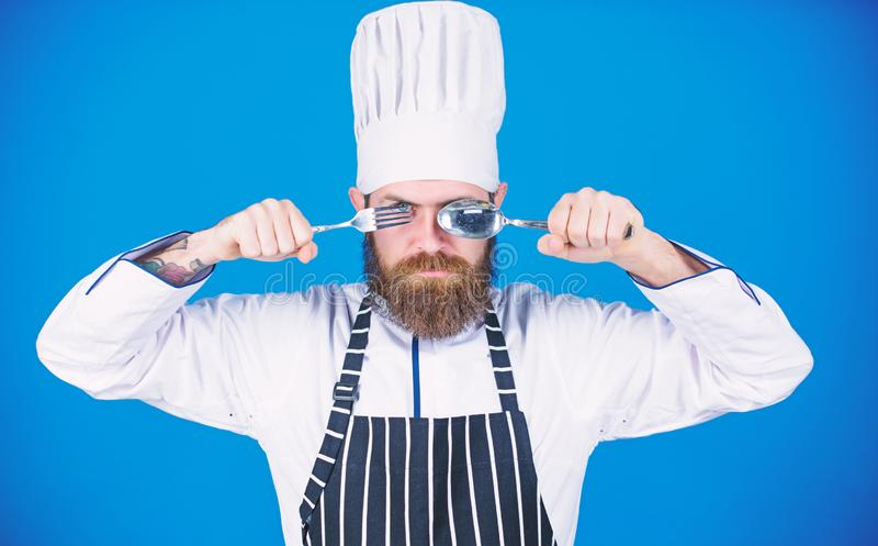 Time to try taste. Chef serious strict face hold spoon and fork. Man handsome with beard holds kitchenware on blue stock image