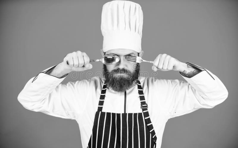 Time to try taste. Chef serious strict face hold spoon and fork. Man handsome with beard holds kitchenware on blue royalty free stock photos