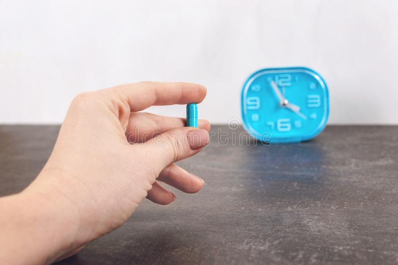 Time to using the Pill. Bright blue capsule pill in women hand on alarm clock background. Female hands holding one capsule stock images