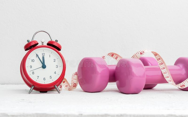 Time to work out, healthy lifestyle and diet concept. Pink dumbbells, alarm clock, and measuring tape on white wood with copy spa stock image
