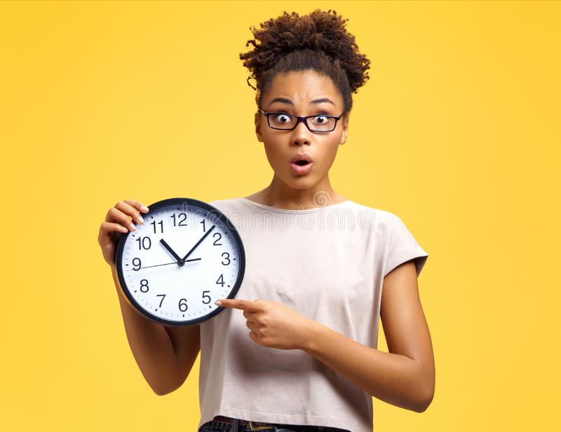 Time to work! Student with shocked face holds clock and points to them royalty free stock image