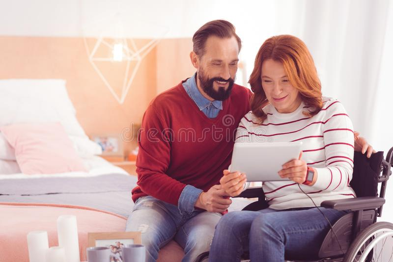 Positive man resting with his disabled wife stock photo