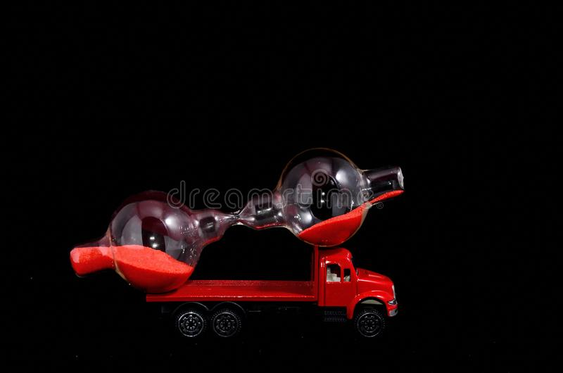 Time Transportation Concept. Hourglass Watch on a Red Toy Truck over Black Background stock photos