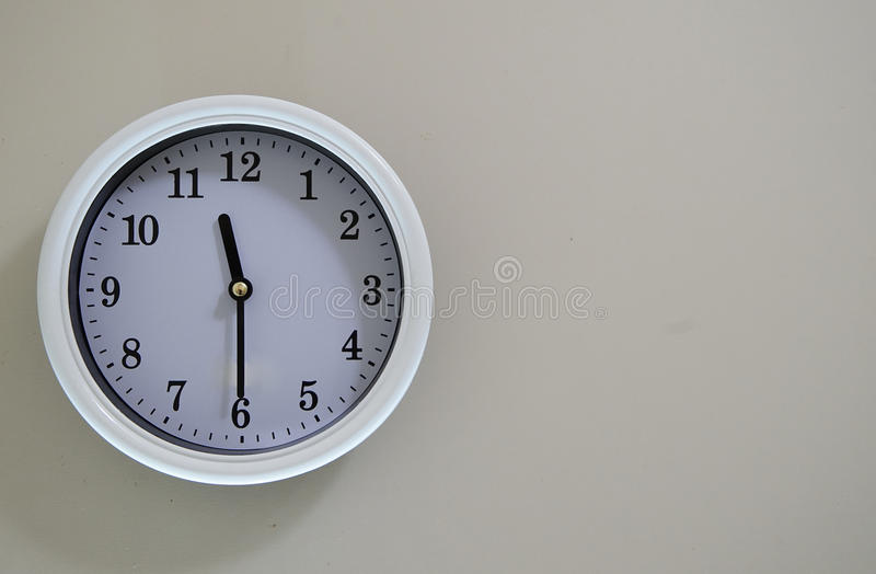 The time of the wall clock is 11:30. The time of the wall clock hanging clock is 11:30 stock photo