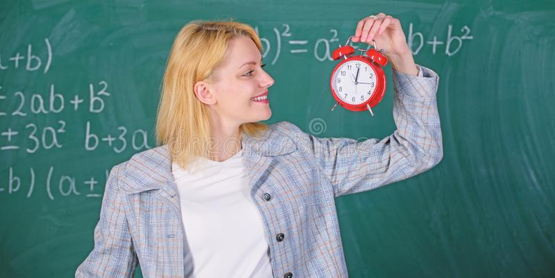 Always on time. Woman teacher hold alarm clock. She cares about discipline. Time to study. Welcome teacher school year royalty free stock photo