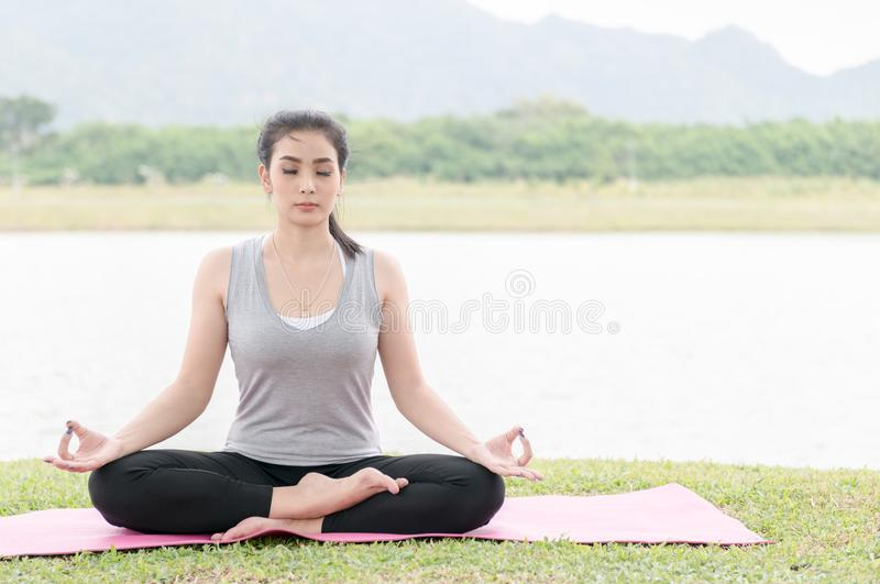 Attractive young woman exercising and sitting in yoga lotus position. Time for yoga. Attractive young woman exercising and sitting in yoga lotus position while royalty free stock photos