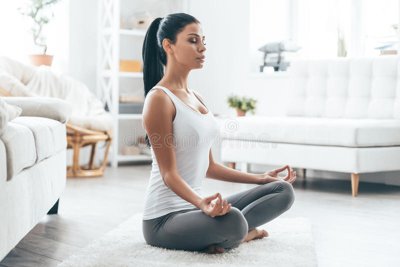Time for yoga. Attractive young woman exercising and sitting in yoga lotus position while resting at home royalty free stock photos
