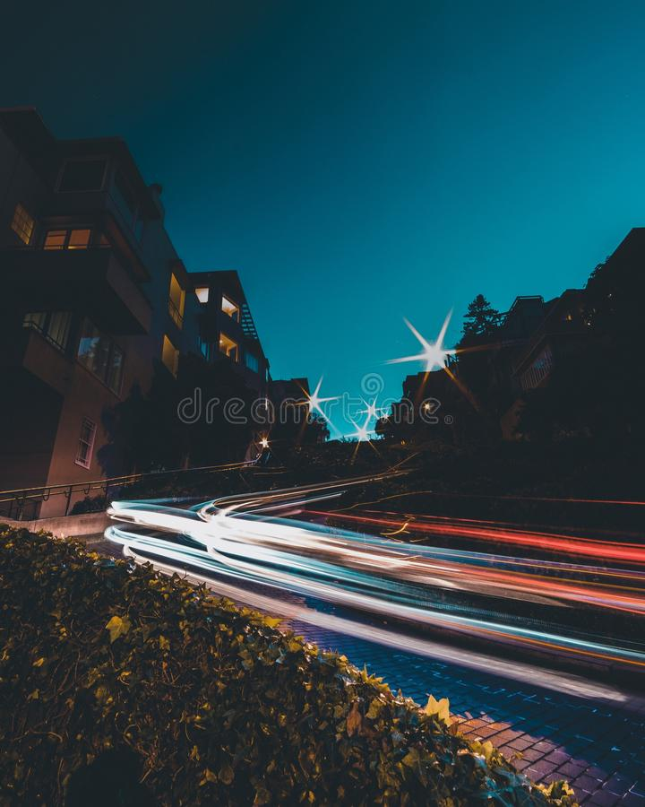 Timelaps of car lights on the road with a blue sky in the background at night time stock image