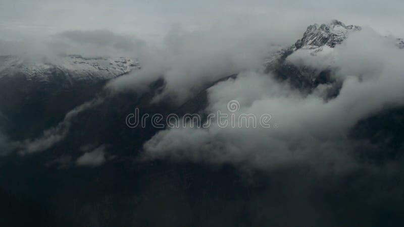 Timelapse av gråa höga blåsa snöberg med stormmoln och stark vind royaltyfria bilder
