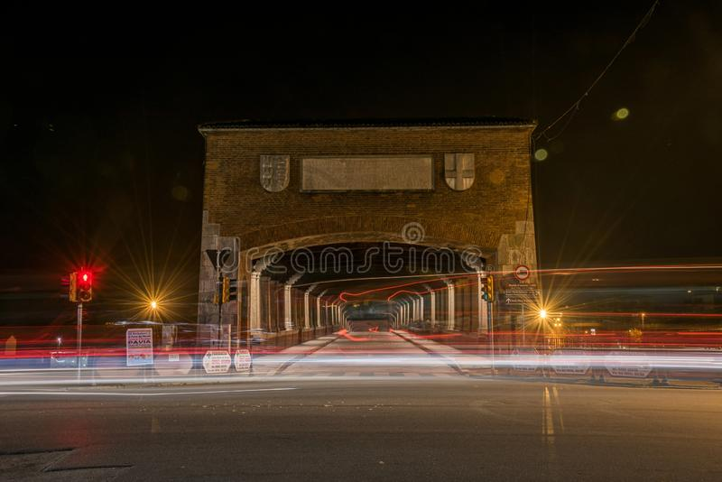 Timelapse di luci dell'auto sulla strada vicino a un tunnel di notte a Pavia, Italia immagini stock libere da diritti