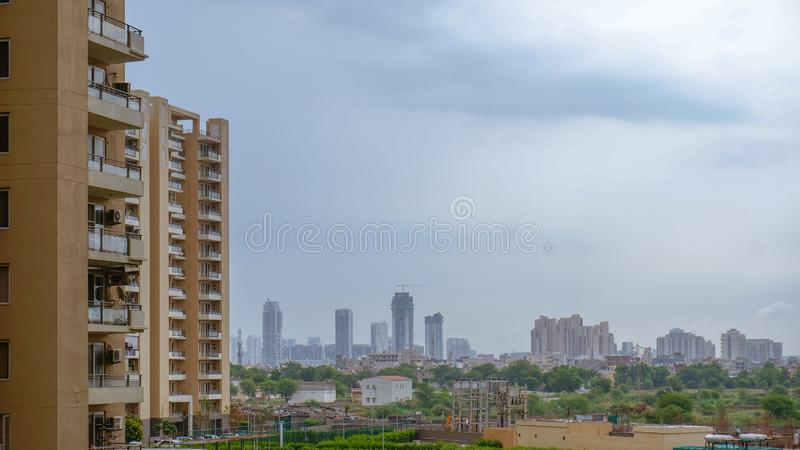 Timelapse of monsoon clouds over the sky scrapers in gurgaon with the sun at dusk shining through. There are apartments in the foreground and in the distance royalty free stock images