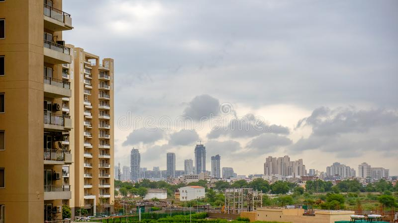 Timelapse of monsoon clouds over the sky scrapers in gurgaon with the sun at dusk shining through. There are apartments in the foreground and in the distance stock photos