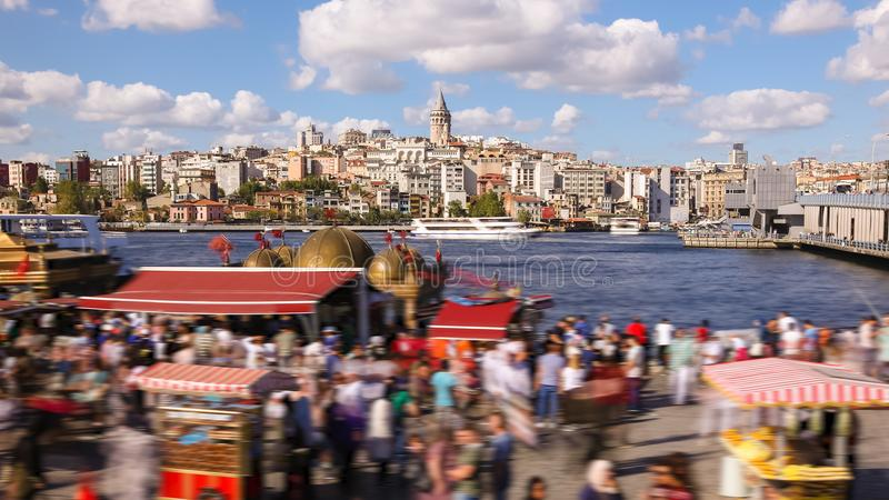 People walking around famoust tourist place in Istanbul with Galata Tower view and Bosphorus. Timelapse oftourist boats in Bosphorus stock photo