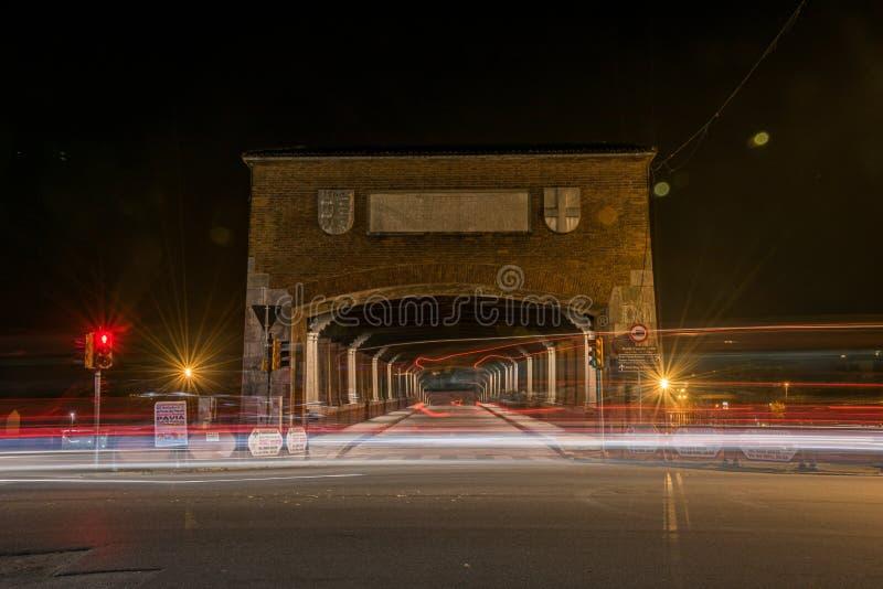 Timelapse-skott på bilbelysning på väg nära en tunnel nattetid i Pavia, Italien royaltyfria bilder