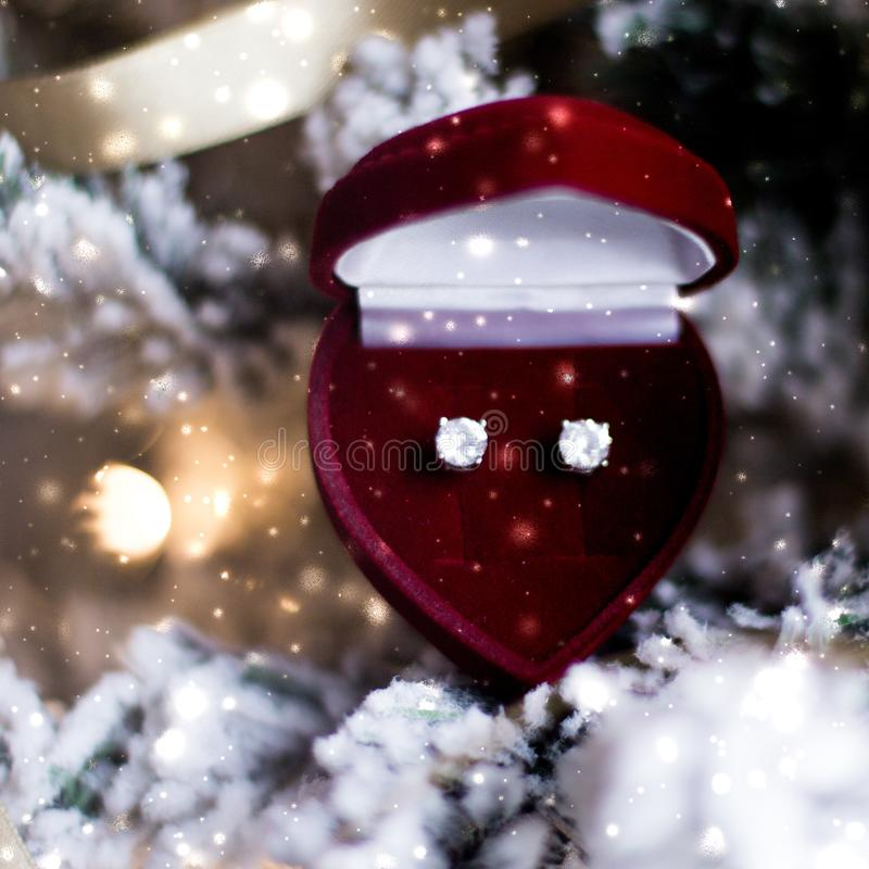 Diamond earrings in heart shaped jewellery gift box on Christmas tree, love present for New Years Eve, Valentines Day and winter. Timeless luxury, romantic stock image