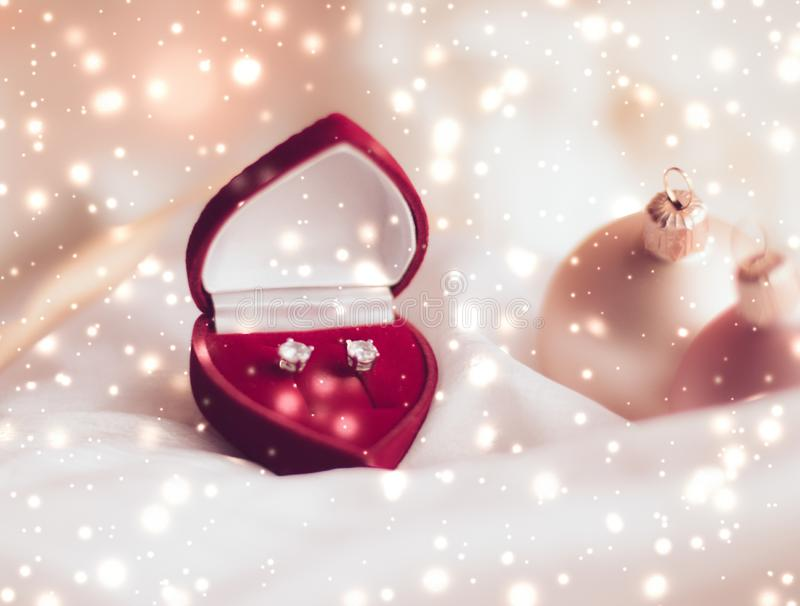 Diamond earrings in a heart shaped jewellery gift box, love present for Christmas, New Years Eve, Valentines Day and winter. Timeless luxury, romantic proposal royalty free stock photography