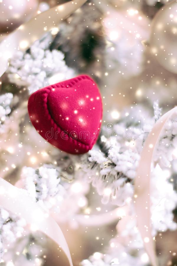 Heart shaped jewellery gift box on Christmas tree, love present for New Years Eve, Valentines Day and winter holidays. Timeless luxury, romantic proposal and stock image